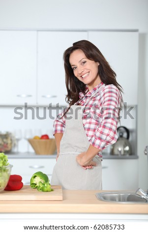 Beautiful woman standing in kitchen - stock photo
