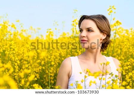 Beautiful woman standing in rapeseed field in bloom - stock photo