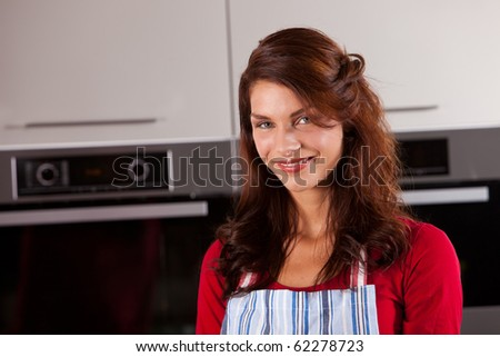 Beautiful woman standing in the kitchen wearing an apron and looking happy - stock photo