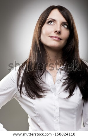 Beautiful woman standing making her plans staring upwards with a serious thoughtful expression, upper body studio portrait - stock photo