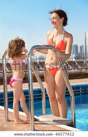 beautiful woman standing near swimming pool and looking at her daughter. - stock photo