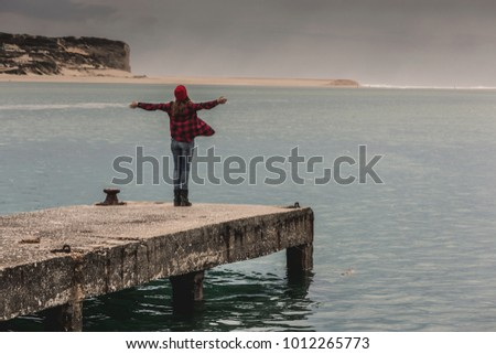 Beautiful woman standing on a pier with arms raised feeling the freedom