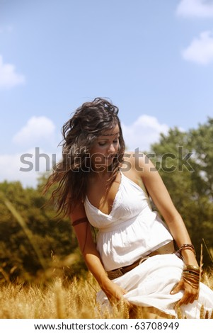 Beautiful woman standing on a wheat field outdoors on a hot summer afternoon. She is wearing a nice white dress and has long brown hair. - stock photo