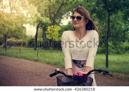 beautiful woman standing on bike with flowers in park and smiling