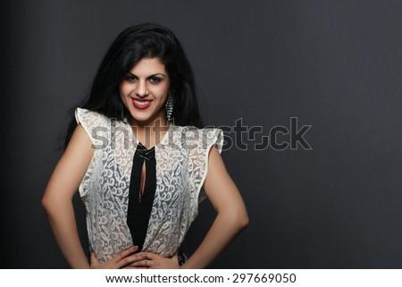 Beautiful woman standing on gray background - stock photo