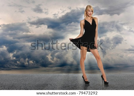 Beautiful woman standing on road against stormy sky