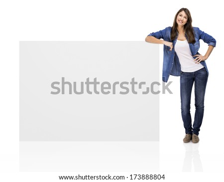 Beautiful woman standing over a blank billboard, isolated over a white background - stock photo