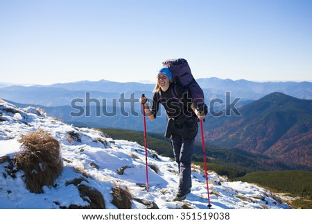 Beautiful woman standing with backpack on the background of mountains.