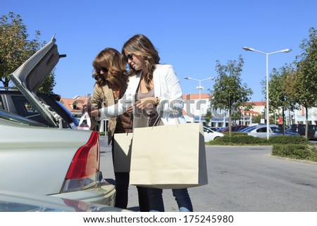 Beautiful woman standing with shopping bags at their car in fashion outlet.  - stock photo