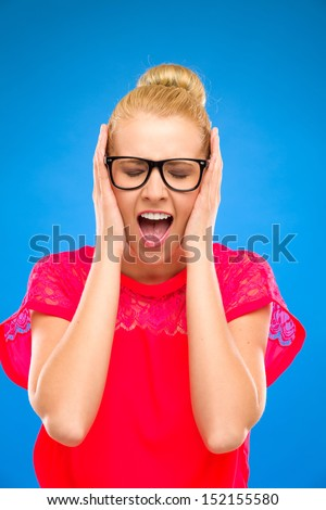 Beautiful woman stops her ears and screaming. Studio shot isolated on blue. - stock photo
