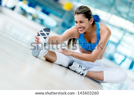 Beautiful woman stretching at the gym looking happy - stock photo