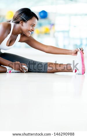 Beautiful woman stretching her leg at the gym  - stock photo