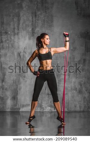 beautiful woman stretching on a studio background - stock photo
