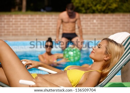 Beautiful woman sunbathing in bikini by swimming pool, smiling. - stock photo