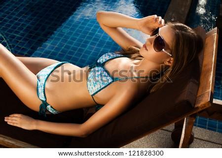 Beautiful woman sunbathing in chair near pool outdoors - stock photo