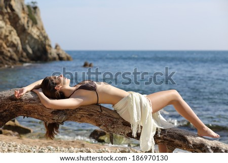 Beautiful woman sunbathing on the beach on vacations with the sea in the background