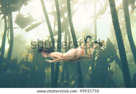 Beautiful woman swimming underwater - stock photo