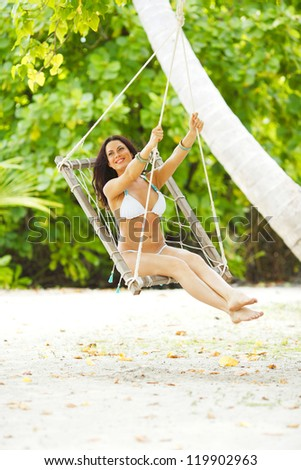 Beautiful woman swinging in beach hammock