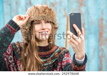 beautiful woman take a picture of herself with a smartphone over wooden background with retro ski. selfie, focus on face - stock photo