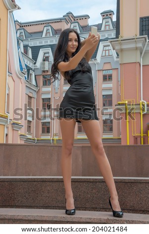 Beautiful woman taken picture of herself, selfie. Beautiful and slender girl talking on a cell phone on a city street. Model in little black dress in front of colorful buildings in a European city - stock photo