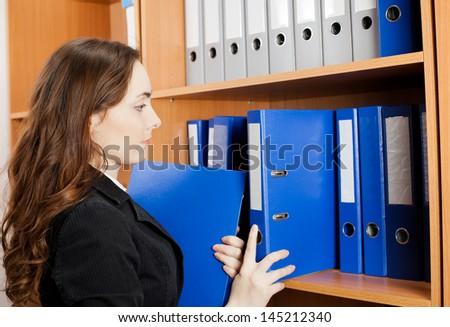 Beautiful woman taking a blue folder from shelf - stock photo
