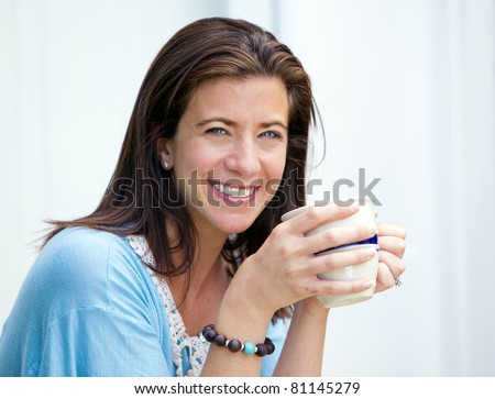 Beautiful woman taking a coffee break holding a mug - stock photo
