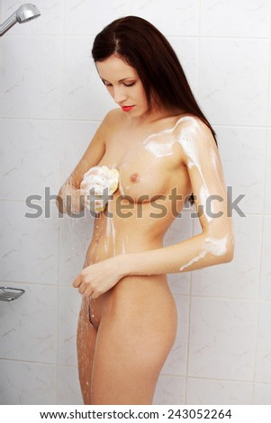 Beautiful woman taking a shower and washing her body. - stock photo