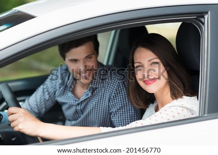 Beautiful woman taking her husband for a drive looking through the open side window of the car with a beaming smile of enjoyment - stock photo