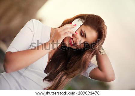 beautiful woman talking by phone near the fountain