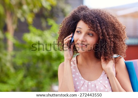 Beautiful woman talking on her phone while out on a shopping spree  - stock photo