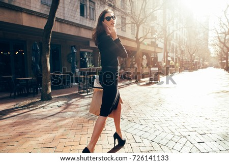 Beautiful woman talking on mobile phone and walking on the city street.