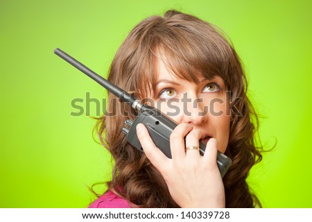 Beautiful woman talking on the walkie-talkie over green background - stock photo