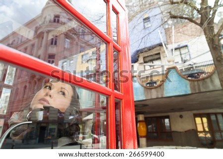 Beautiful woman talking over the phone in old-fashion booth in the modern district Of Vienna - stock photo