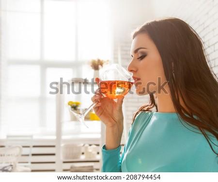 Beautiful woman tasting a glass of rose wine. - stock photo