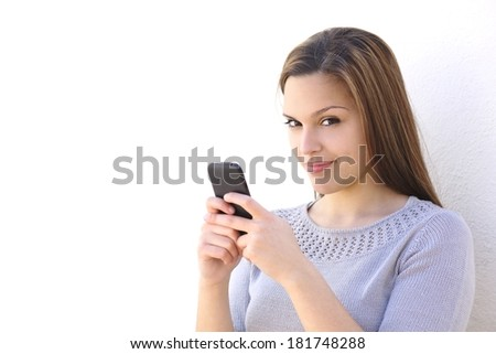 Beautiful woman texting on a smartphone and looking at camera on a white wall
