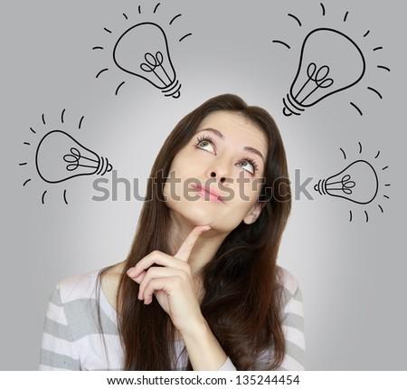 Beautiful woman thinking many ideas and looking up on grey background - stock photo