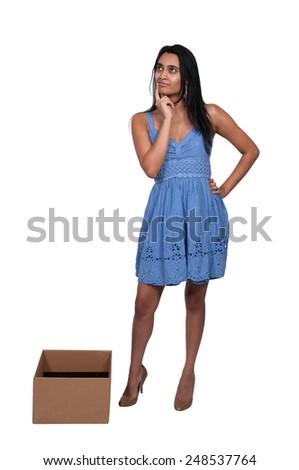 Beautiful woman thinking while standing inside a box - stock photo