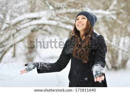 Beautiful woman throws snow in park - stock photo