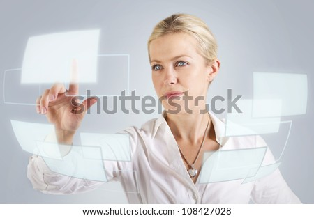 Beautiful woman touching a digital screen, panel, hologram