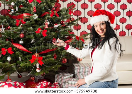 Beautiful woman touching natural Chrismas tree in her home - stock photo