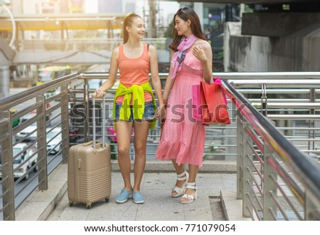 Beautiful woman tourists walking and carry luggage with shopping bags in the city downtown,shopping and traveling concept.