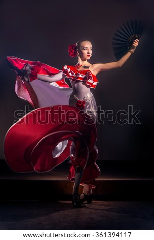 Beautiful Woman traditional Spanish Flamenco dancer dancing in a red dress with black fan