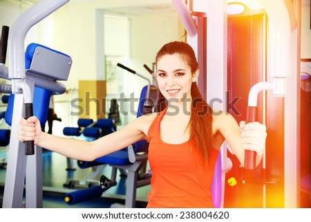 Beautiful woman training with weights in gym - stock photo