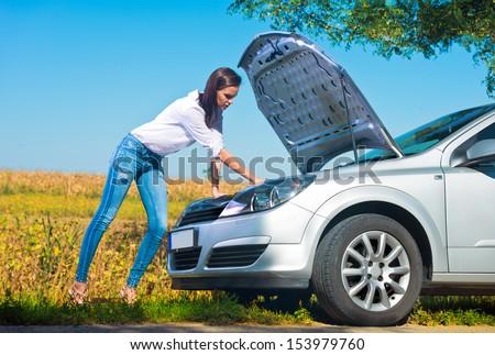Beautiful woman trying to repair a broken car - stock photo
