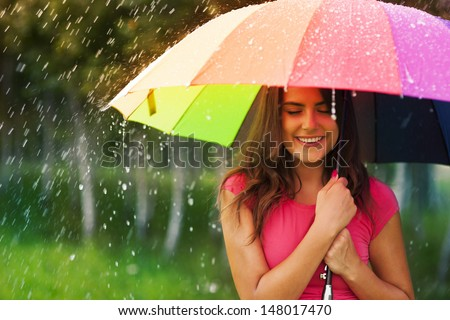 Beautiful woman under rainbow umbrella - stock photo