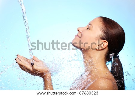 Beautiful woman under splash of water against blue background - stock photo