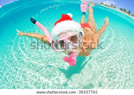 beautiful woman underwater with snorkel and christmas hat