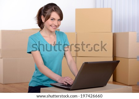 Beautiful woman using a laptop while unpacking box at home - stock photo