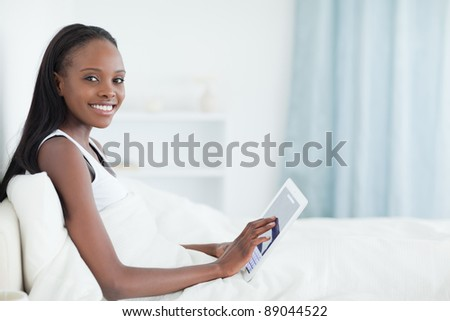 Beautiful woman using a tablet computer in her bedroom - stock photo