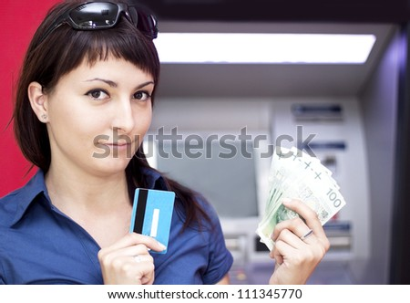 Beautiful woman using credit card, she is withdrawing money from an ATM machine. - stock photo